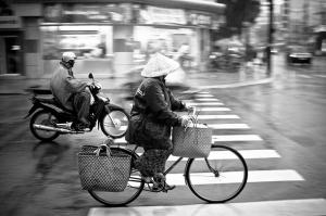 Vietnamese Woman Cycling In The Rain